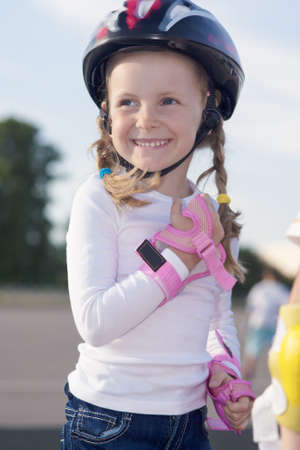 portrait of small little caucasian girl wearing protective helmet while skating on track outdoors photo