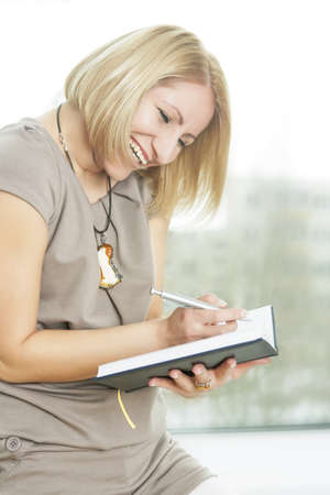 cute portrait of a blond girl having attire making notes on notebook and smiling Stock Photo