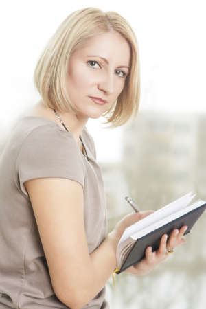 making notes: serious portrait of a blond girl having attire making notes on notebook and smiling