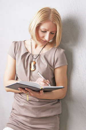 making notes: cute portrait of a blond girl having attire making notes on notebook and smiling Stock Photo
