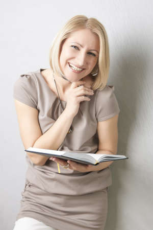 making notes: portrait of a smiling happy blond woman laughing and making notes on notebook Stock Photo