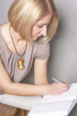 portrait of a blond girl thinking and making notes on notebook photo