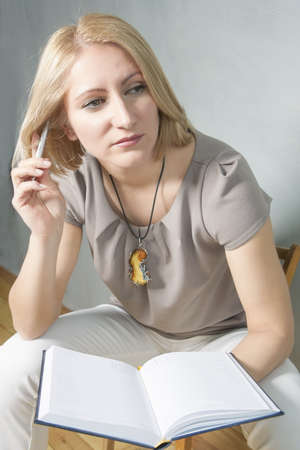 making notes: portrait of a blond girl thinking and making notes on notebook Stock Photo