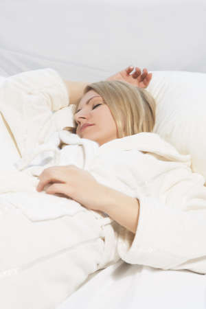 portrait of a cute relaxing young caucasian blond woman lying on bed and sleeping photo