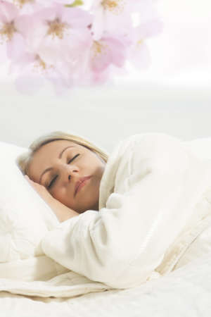 portrait of a cute relaxing young caucasian blond woman lying on bed and sleeping with a smile on her face over artistic background Standard-Bild