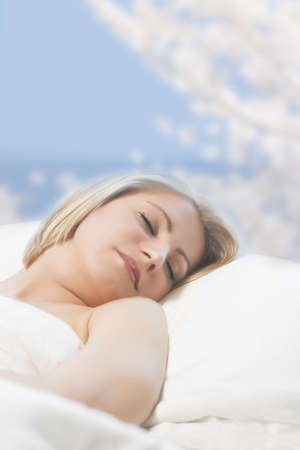 rested: portrait of a cute relaxing young caucasian blond woman lying on bed and sleeping with a smile on her face over artistic background Stock Photo
