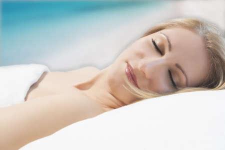 good night: retrato de una linda joven relajado, cauc�sico, mujer rubia tumbada en la cama y dormir con una sonrisa en su cara sobre el fondo art�stico con una exposici�n larga
