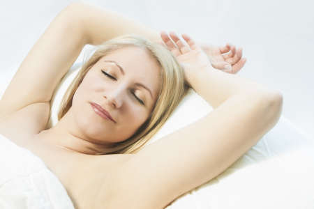 30 35 years women: portrait of a cute relaxing young caucasian blond woman lying on bed and sleeping with a smile on her face using a long exposure