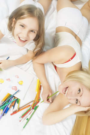 10 years girls: portrait of mother and little daughter togerther lying on bed and having fun with drawing pictures using color pencils