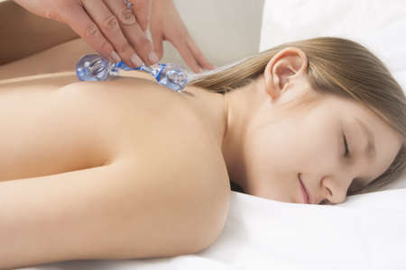 little young caucasian girl is beeing treated with a massage lying on white linen downwards Stock Photo - 15530218
