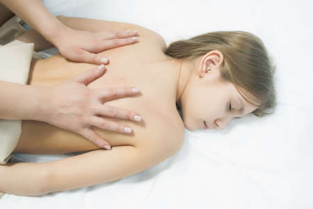 little young caucasian girl is beeing treated with a massage lying on white linen downwards photo