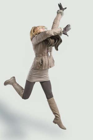 salto largo: mujer rubia joven salta arriba con las manos levantadas hacia arriba y con ropa de invierno Foto de archivo