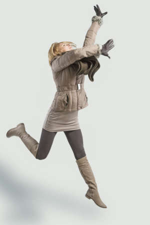 young blond woman jumping high with hands lifted up and wearing winter clothes