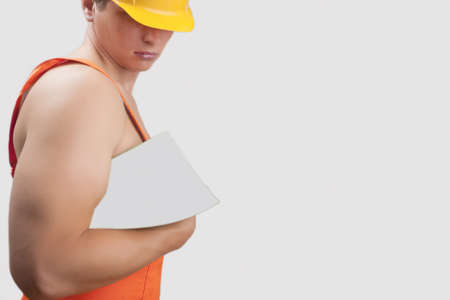 well equipped: portrait of a strong builder handsome in protective helmet holding papers in hand over white background