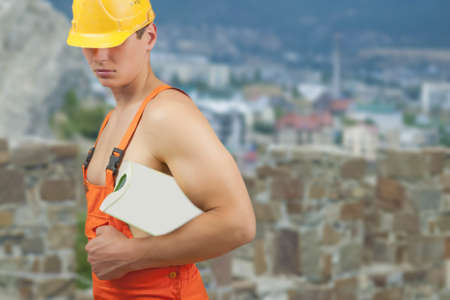 well equipped: portrait of a strong builder handsome in protective helmet holding papers in hand over artistic background