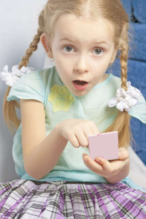 exclaiming: cute little fasionable girl applying decorative cosmetics indoors and exclaiming