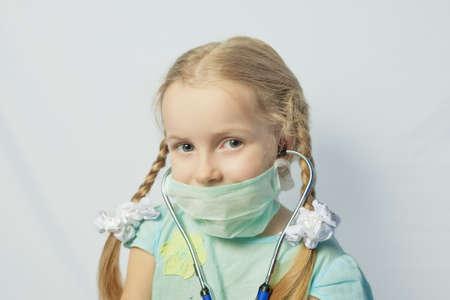 medical mask: ni�a rubia cauc�sica con una m�scara m�dica sobre fondo brillante