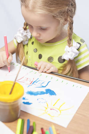 portrait of a little caucasian blond girl making drawing using colorful pencils  and paint indoors Stock Photo - 16411189