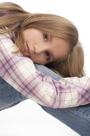10 to 12 years: lovely portrait of cute smiling caucasian blond girl sitting on floor with hands elongated along legs isolated over white background Stock Photo