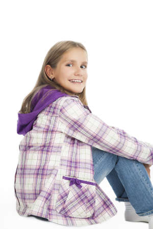 10 years girls: lovely portrait of cute smiling caucasian blond girl sitting on floor with hands put on  legs isolated over white background
