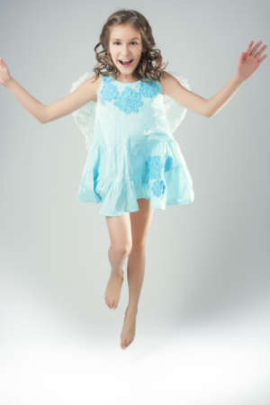 10 12 years: lovely portrait of cute little girl wearing angels wings and jumping high