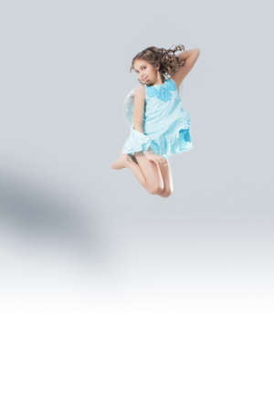 lovely portrait of cute little girl wearing angels wings and jumping high photo