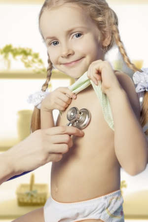 examine: young and smiling caucasian little girl is being treated by doctor using stethoscope Stock Photo