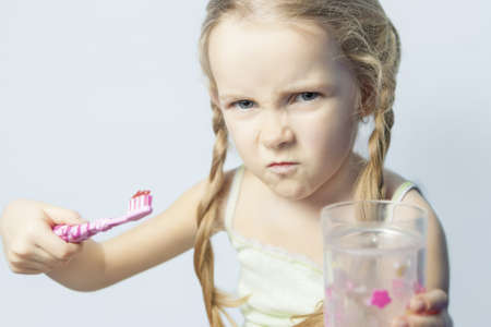 willing: angry and furiuos little girl not willing to brush her teeth over isolated background