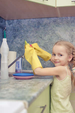 little blond girl makes dishes cleaning using water and sponge shot in household environment photo