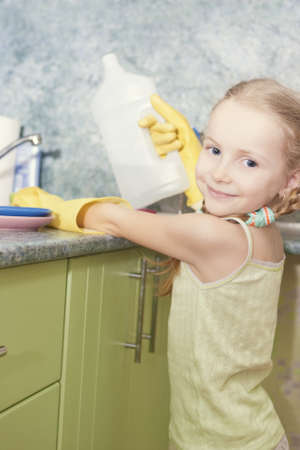 little blond girl makes dishes cleaning using water and sponge shot in household environment Stock Photo - 18384098