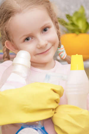 positive and natural candid portrait of young little girl with cleaning liquids bottles smiling shot in household environment photo