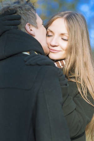 young caucasian couple kissing and standing together outdoor photo