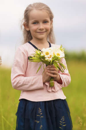 natural portrait of young cute little girl standing outside with flowers bunch photo