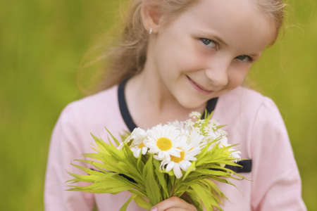 closeup portrait of little caucasian girl with flowers bouquet standing outside photo
