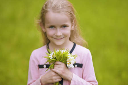portrait of little girl holding flowers bunch and smiling outside. horizontal shot photo