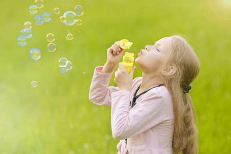 portrait of cute little girl blowing soap bubbles outside. horizontal shot