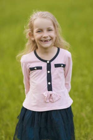 lovely portrait of cute little blond girl showing   positive emotions outside photo