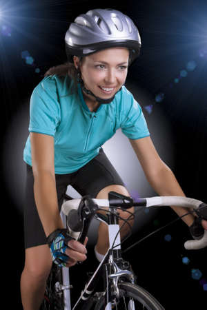 portrait of  woman riding bike over isolated background  model equipped with a professional biking gear, uses professional race bike  vertical shot photo