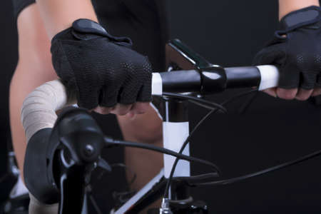 closeup of hands and handlebars of a professional biking female athlete shot in studio  isolated over black  horizontal shot photo