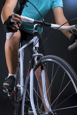 closeup of legs and race bike of a professional  female athlete shot in studio  isolated over black  vertical shot  composite image Stock Photo