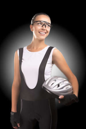 beautiful portrait of caucasian female bike athlete wearing professonal sportswear and smiling. isolated over black background. vertical shot photo