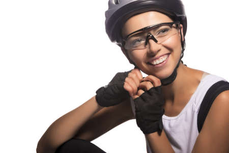 portrait of professional female bike athlete sitting and fixing her protective helmet.isolated over pure white background. horizontal image photo