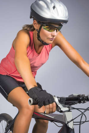 female cycling athlete riding mountain bike and equipped with professional bike gear isolated over gray. vertical shot photo