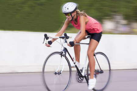 woman cycling outdoors. panning technique used.horizontal shot