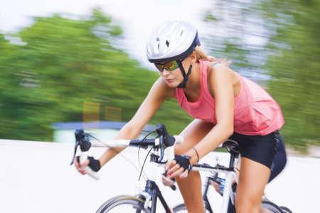 panning shot: giovane donna femminile di razza caucasica andando in bici da corsa all'aperto. tecnica panning utilizzato. tiro orizzontale