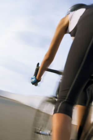 panning shot: leg of a professional female cyclist making a race outdoors. vertical shot. panning