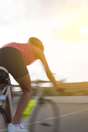 panning shot: back of a female athlete cycling on a track. blurred motion, panning. vertical shot