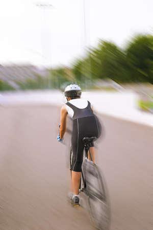 panning shot: posteriore di una bicicletta atleta femminile su un binario. Immagine mossa, panning. colpo verticale