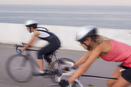 panning shot: two professional female athletes compete in bike race outdoors. blurred  image bacause of panning Stock Photo