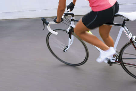 panning shot: professional female cyclist making excercise on race bike on the track. image with panning.horizontally oriented image